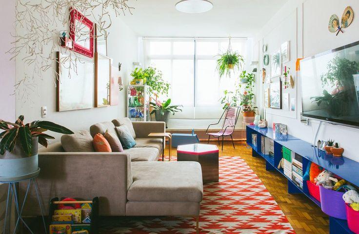 Sala de estar com muitas cores, quadros e objetos bacanas e plantas.