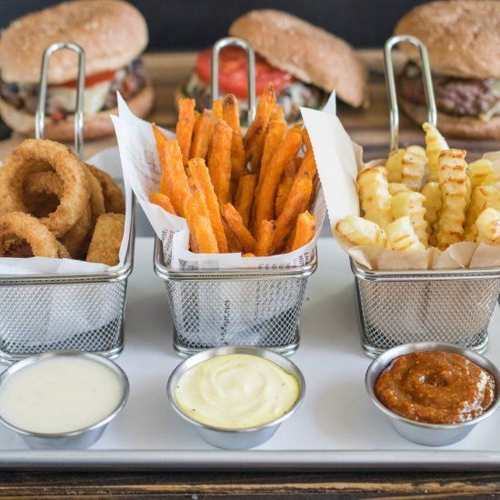 Fries and onion rings with German cheese dip, French truffle aioli dip, British curry ketchup