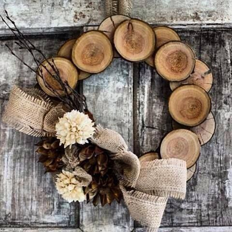 Wooden disk wreath, adorned with pine cones, and a beautiful burlap bow.