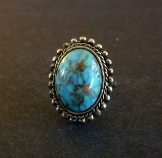 Elegant vintage faux turquoise southwestern style adjustable cocktail ring. It features a large blue oval marbled glass cabochon. The stone lies in a nice silver tone setting.     Size: Adjustable. Presently set at 7.5    Condition: Excellent. There is some surface wear on the finger band.