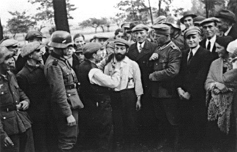 After Germany invades Poland in September, 1939, German soldiers enjoyed the public humiliation of Polish Jews. One Jew is forced to cut the beard of another under German supervision as the local population of Tomaszow Mazowiecki, Poland watches.