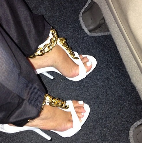 white sandal decorated with bulky gold chain