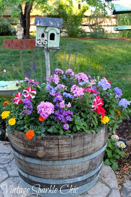a wine cask full of flowers and a birdhouse that's seen better days; yes.