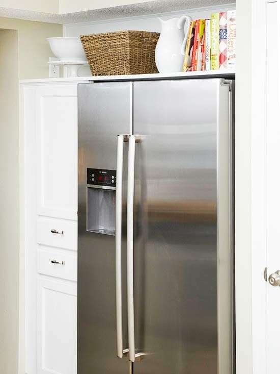 Appears to be built in fridg....what we want.  A base cabinet topped with an upper cabinet makes a column of useful storage. One large shelf spanning the length of the niche creates a useful space for storing cookbooks and large servingware. The result is a boost of storage real estate, as well as the look of a pricey built-in refrigerator for a lot less.