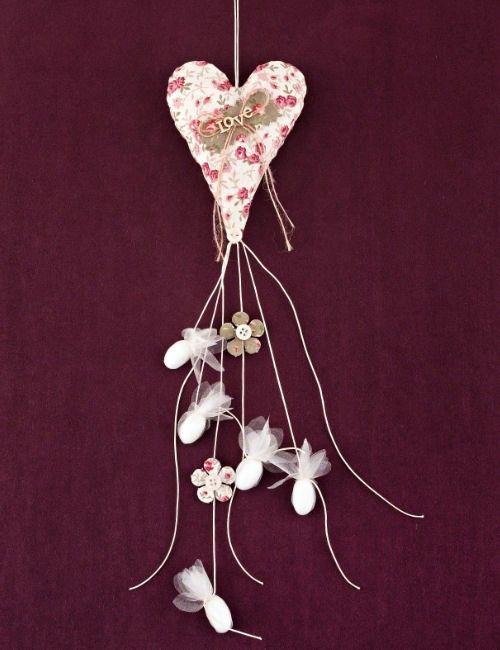 Μπομπονιέρες γάμου φλόραν φουσκωτή καρδιά  Διαστάσεις : 13Χ10 εκ  Η τιμή αφορά έτοιμη δεμένη μπομπονιέρα με 5 κουφέτα αμυγδάλου Χατζηγιαννάκης.  Κρεμαστή μπομπονιέρα γάμου καρδιά φουσκωτή στενόμακρη από φλοράλ ύφασμα, με διακόσμηση χακί μπάλωμα, ξύλινο Love και φλοράλ λουλούδια και κρεμαστά κο