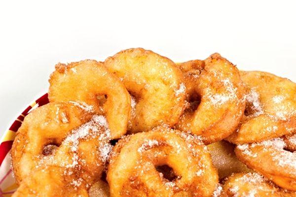 Recept na Smažená jablíčka. Kolečka jablíček obalená v těstíčku a usmažená dozlatova, servírovaná posypaná skořicovým cukrem.