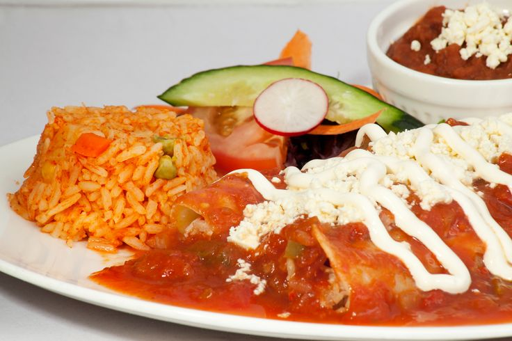 Enchiladas de Pollo: Two hand rolled enchiladas filled with chicken. Served with rice, frijoles bayos