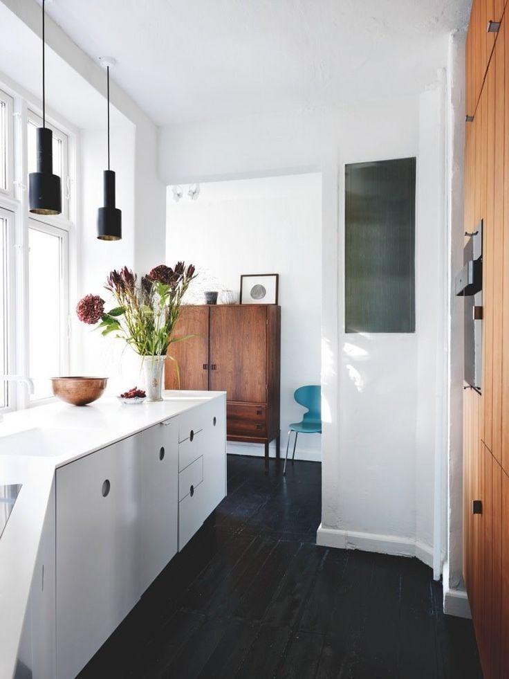 beautiful white kitchen with dark flooring