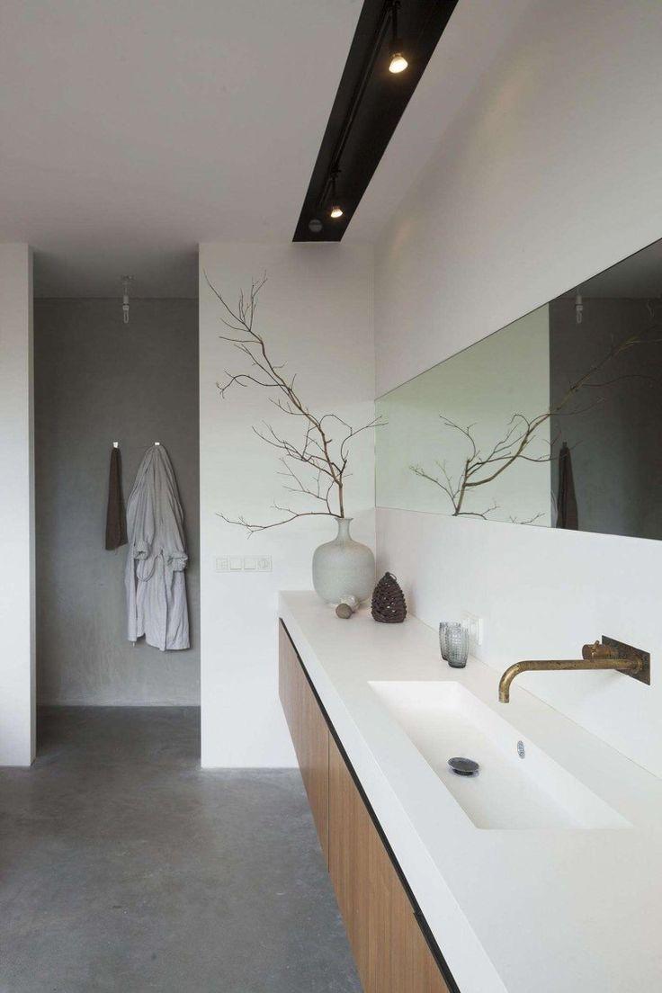 revêtement de sol effet béton ciré et meuble sous-vasque en bois massif dans la salle de bains blanche