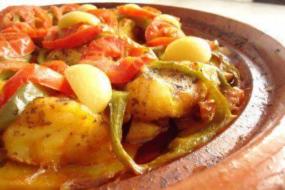 Tajine van kabeljauw met groenten 1 ajuin 1 teentje knoflook 1 tomaat 1 wortel 2 aardappelen 1 rode paprika 1 gele paprika 6 takjes verse koriander 500 gr kabeljauwfilet (of moten) 1 theelepel gemalen komijn 1 pakje saffraan 1 theelepel paprikapoeder zout en zwarte peper 6 soeplepels olie