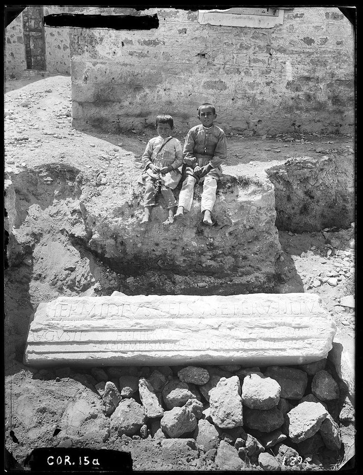 Inscribed epistyle block ; in the background, schoolhouse with boys Date:   1896 Area:   Early Excavations Site:   Corinth City:   Ancient Corinth Country:   Greece