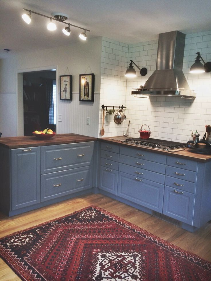 My IKEA Bodbyn grey kitchen. Karlby walnut countertops, range hood, matte white subway tile, grey grout, Schoolhouse Electric sconces, vintage Persian rug, pop art...all DIY!