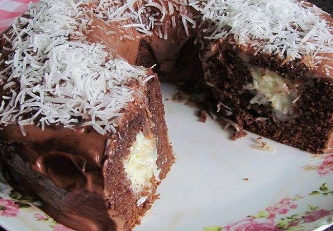 Bolo surpresa de chocolate com recheio de beijinho de coco e coberto com calda de chocolate e coco
