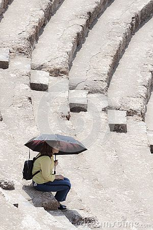 Tourist is sitting in the amphitheater of the antique greek, later roman, city of Ephesus; in the actual Turkey