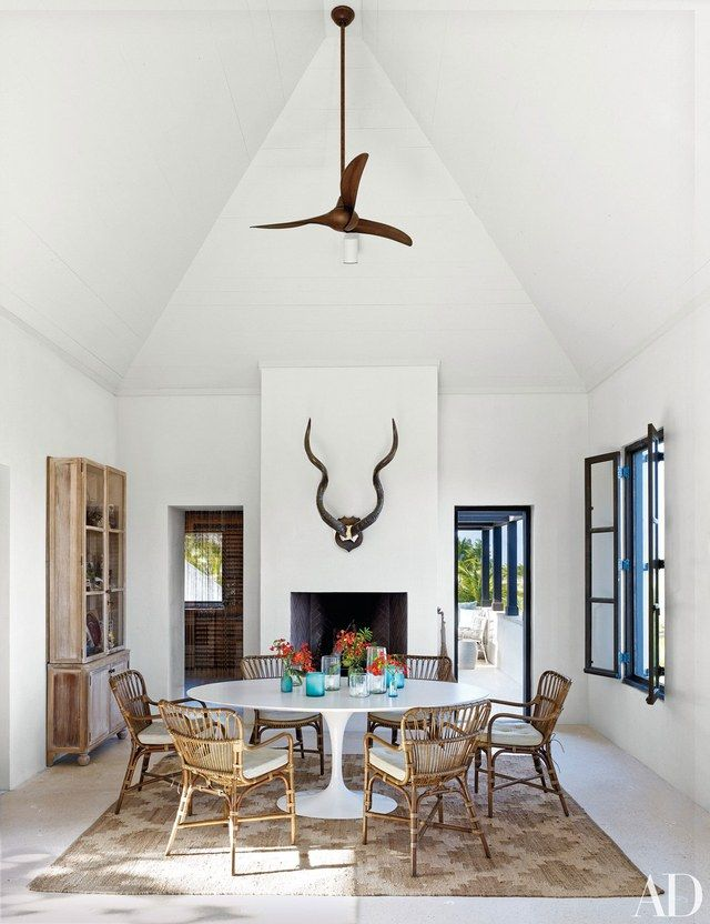 Rattan armchairs by Palecek nestle up to a vintage Saarinen table in the dining room | archdigest.com
