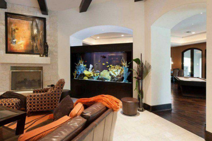 aquarium maison en tant que séparation dans la salle de séjour avec une cheminée en pierre et canapé en cuir