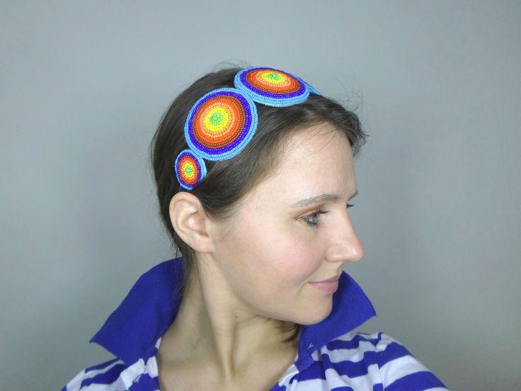 Rainbow Round Čelenka Rainbow Round je inspirována barevností a pestrostí duhy.  Čelenka je vyšita na šesti plstěných kotoučích. Ke korálkové výšivce byl požit kvalitní rokajl Preciosa v barvách světle a tmavě modrá, hnědá, červená, oranžová, žlutá a zelená. Konce kovového základu čelenky jsou opatřeny tmavě modrou sametovou stužkou.