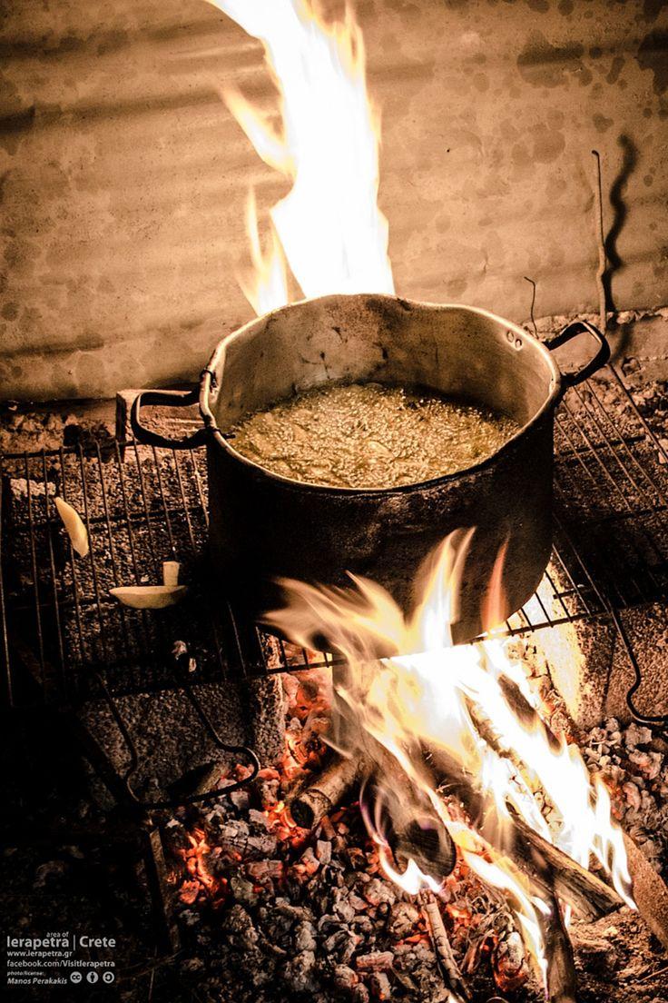 Deep frying Cretan potatoes in olive oil on the hearth