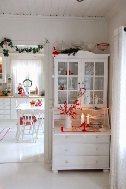 biały skandynawski kredens z czerwonymi dekoracjami świątecznymi