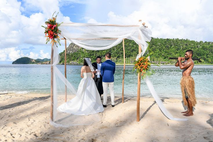 Wedding ceremony by the beach with wood poles and flower for the arch Paradise Cove Island Resort, Yasawa, Fiji. Photographed by Anais Photography.