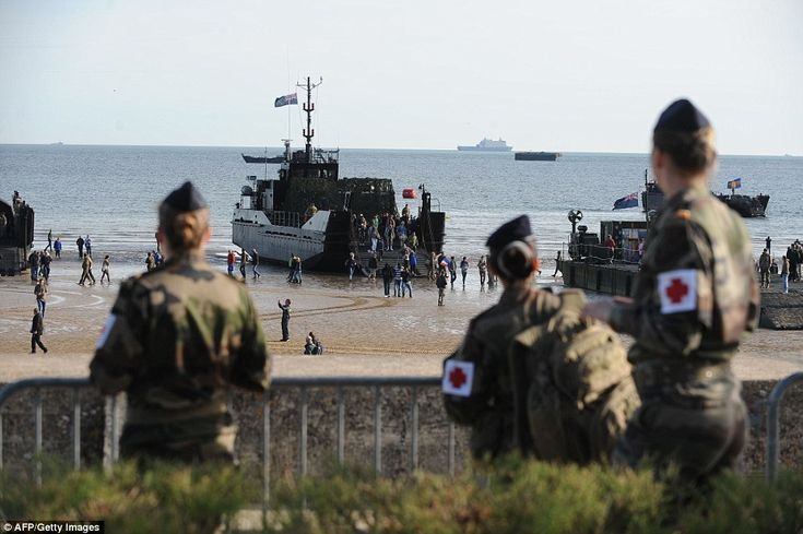 Echoes of the past:  People walk on the beach alongside WWII ships prior to the start of a...