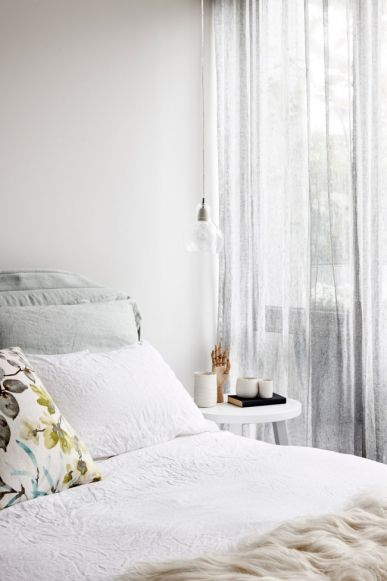 Delicate 'Mega Bulb' pendants by Sofie Refer float above side tables by Gervasoni. The 'Cloudscape Platform 160' bed by Diesel is coordinated with soft, sheer grey curtains.