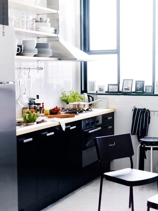 Glossy black lower cabinets, open white upper cabinets and tile. A great background to pops of colour.