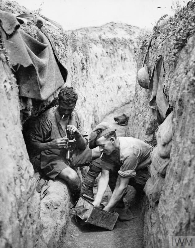 Two men of the 42nd Canadian Infantry Battalion (Royal Highlanders of Canada) clean a Lewis Gun in a reserve trench during the Third Battle of Ypres, November 1917.