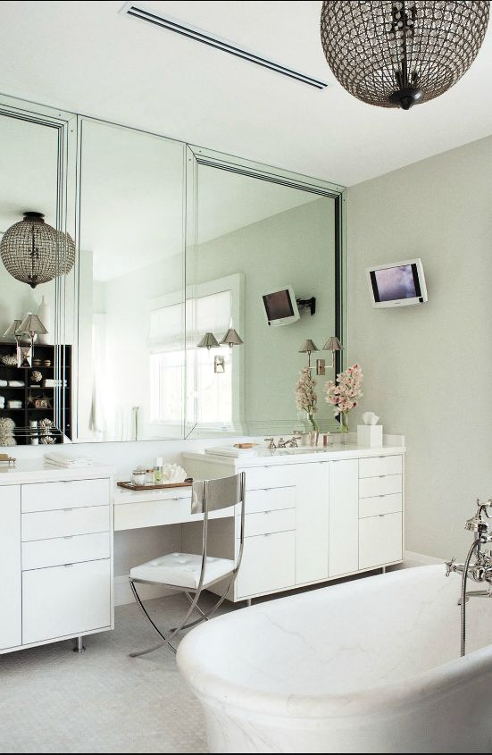 Vanity to ceiling mirrors really open up this bathroom.  Simple cabinetry keeps the focus on the light & the height.