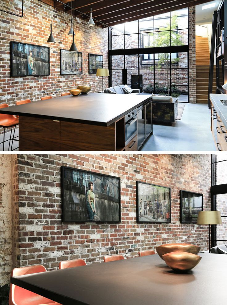 This large kitchen island features concrete pendant lights hanging above and plenty of room to seat four people. Behind the island and the living room, is a brick wall that ties back into the days when the space was used as a commercial garage.