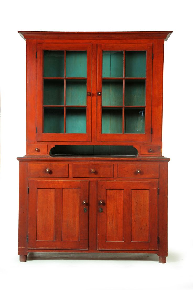 """STEPBACK CUPBOARD.  Possibly Ohio, 1820-1860, cherry and poplar. Two-piece, the upper section with six-pane doors, small drawers, and old blue paint on the interior; the lower section with three drawers over two paneled doors, resting on turned feet. Inlaid knobs. Retains its original red wash with fine color and surface. 82.5""""h. 56""""w. 20.5""""d."""