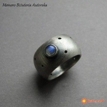 Awangardowa obrączka wykonana ze srebra pr. 930,oksydowana i przecierana. Dziurki ręcznie wiercone. Labradoryt śr. 4 mm z niebieska polaryzacją. Szerokość obrączki- 10 mm. Z uwagi na nietypowy obły kształt obrączka pasuje na palce rozm. 10,5-11, średnica wew. 16,2 mm. Polecam na szczupłe palce lub palec serdeczny. Próba srebra wybita wewnątrz.  www.KuferArt.pl