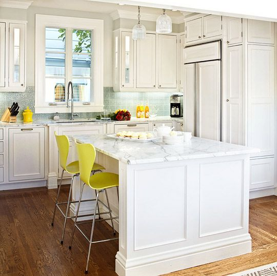 Beautiful, Efficient Small Kitchens | Traditional Home - Youthful Eat-In Kitchen  White paint, marble countertops, and a sparkling blue backsplash give this kitchen a youthful glow. A large center island doubles as a dining table, while the simple molding on the cabinetry and windows keep the space feeling fresh.