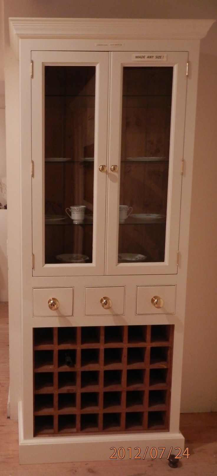 Glazed double display doors and a hearty solid wood wine rack underneath give the traditional kitchen dresser a twist.--Glass Cupboard with Wine Rack & Small Drawers  1000mmW X 340mmD X 2100mmH Unfinished: £1195 complete Stained & Lacquered: £1430 complete Handpainted In Farrow & Ball Colour Of Choice: £1725 complete A
