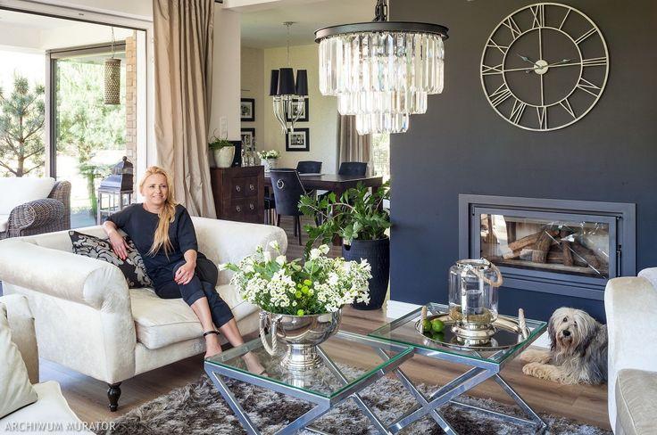 Elegancki, klasyczny salon: ścianę na której znajduje się kominek pomalowano na kolor ciemnoszary, który znakomicie podkreśla klasyczny wystrój wnętrza i jest dobrym tłem do wyeksponowania dekoracjnych dodatków. Pani domu sama zaprojektowała aranżację salonu, wiele mebli odnowiła i przerobiła.