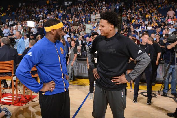 Brandon Rush of the Minnesota Timberwolves talks with Ian Clark of the Golden State Warriors before a game on April 4 2017 at ORACLE Arena in Oakland...