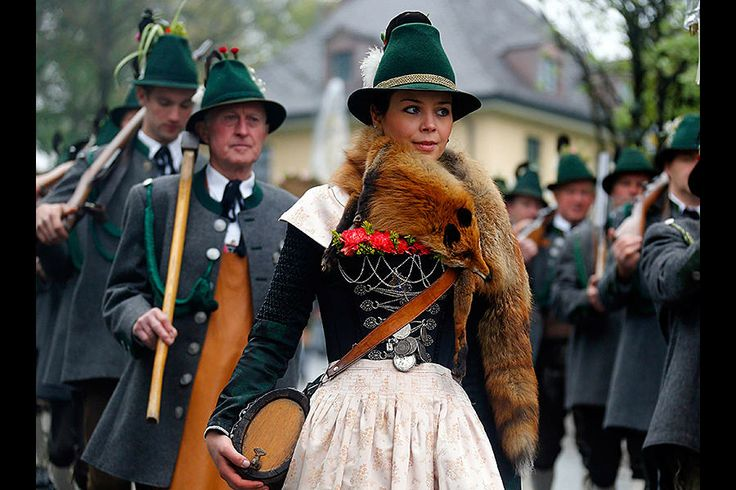 : A Bavarian woman walks among mountain riflemen in traditional outfits during a parade in the southern village of Miesbach, Germany, Sunday. About 5,000 mountaineers from Bavaria joined the traditional annual parade to honor the Patron of Bavarian mountain rifleman. Michael Dalder/Reuters