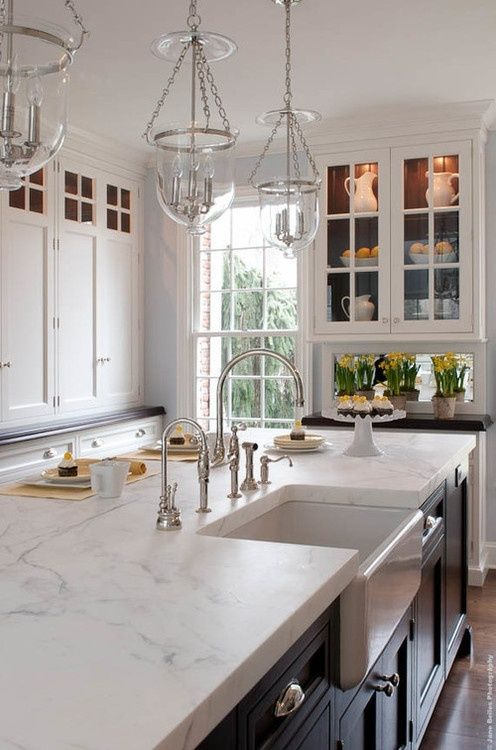 This classic kitchen features white cabinetry around the perimeter of the kitchen with gorgeous walnut countertops and mirrored backsplash while the island has black painted cabinets and a thick marble countertop.