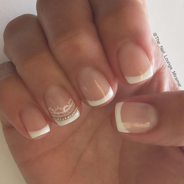 Simple yet elegant white French tips. Give your classic French tip designs a twist by adding silver beads aligning the tip and small details painted in white polish.