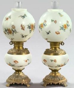 lighting, America, Pair of American gilt brass mounted white opal glass kerosene parlor lamps, fourth quarter 19th century, retaining the period spherical opal glass shades and blown glass chimneys, the opal glass fonts and shades with polychromed floral sprigs. Circa 187501900