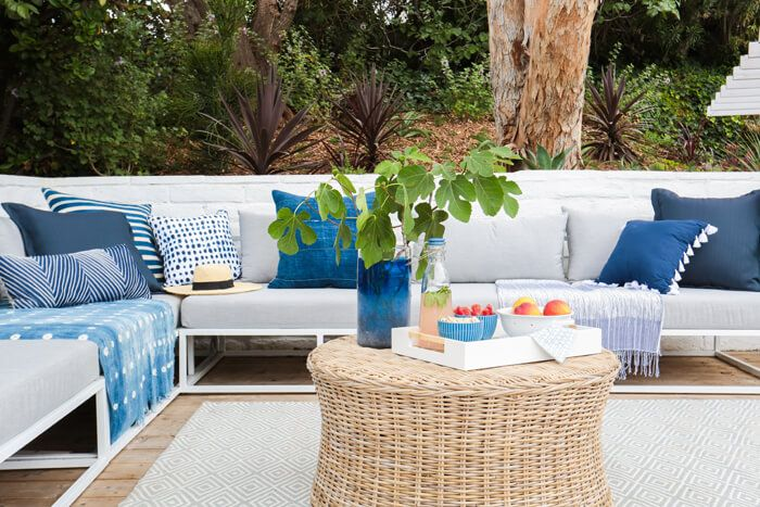 CB2 outdoor sofa with blue and white pillows, rattan table