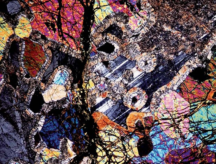 """LACE"":    The mineral olivine, when viewed under an optical microscope, becomes a collage of colorful lines and patterns. In this image you can spot the stone's veins and grains—some beginning to corrode...."