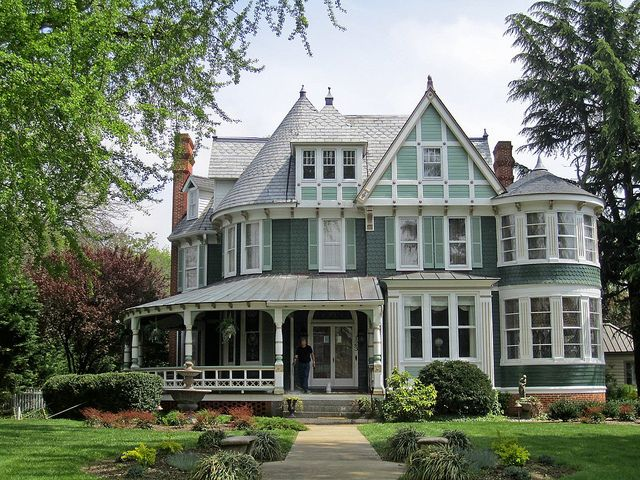 Don't you know the rooms in this short tower are light-filled? Queen Anne style house in Centreville MD has great porch and a wonderful lot of windows.  Too much white; needs something besides green and white.  Gorgeous landscaping.  The setting is beautiful for this home.