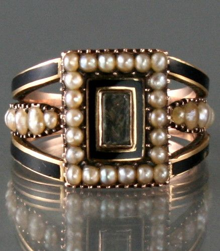 Rare Georgian 9 carat rose gold mourning ring set with a central crystal glass compartment with hair under surrounded by seed pearls and black enamel , there is black enamel and pearls to the shoulders .