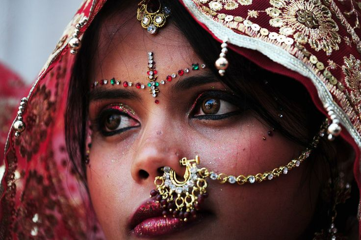 Una novia india observa mientras ella y otras diez mujeres esperan para casarse a sus novios en su ceremonia de boda en un templo local hindú en Nueva Delhi hoy  3 de marzo de 2014. Once parejas se casaron al mismo tiempo. (AFP  / Roberto SCHMIDT)
