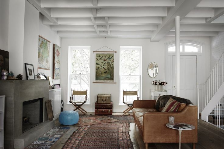 The lofty and bright parlor level is subtly textured with hand-finished plaster walls, a steel stair, and whitewashed ceiling beams.