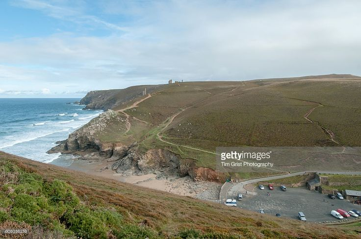 The beach and car park at Chapel Porth, Cornwall with the Wheal Coates tin mine on the cliffs above.