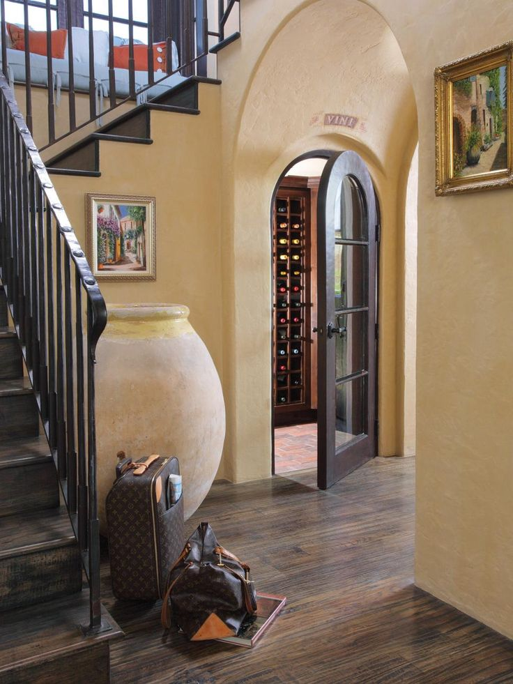 A Wine Cellar Tucked Under The Stairs Behind An Arched