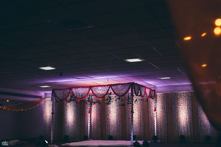 The wedding venue decorated with sweet creams, green and rich red flowers