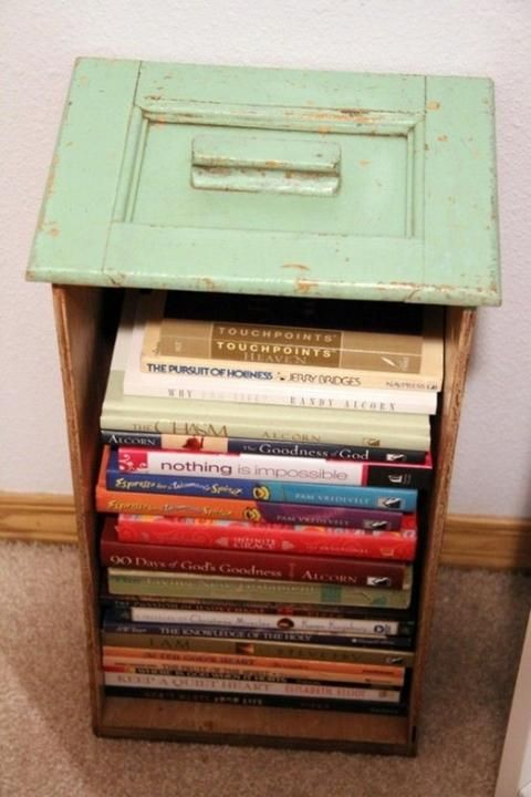 Vintage drawer used to hold books. This would be great on the wall too.